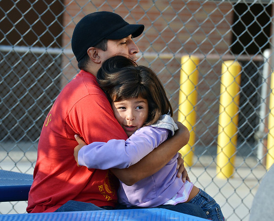 Liliana Escalante, 5, right, gives her father, Armando a hug before start ing the first day of kindergarten at Kohl Elementary School on Friday. Curtis' father Philip looks on in the background.<br />  August 17, 2012<br /> staff photo/ David R. Jennings