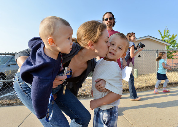 Jennifer Allen holding her son Eli Heffington, 8 months-old, gives her son Paul Curtis, 5, a kiss for the start of the first day of kindergarten at Kohl Elementary School on Friday. Philip Curtis, Paul's father, is in the background.<br />  August 17, 2012<br /> staff photo/ David R. Jennings