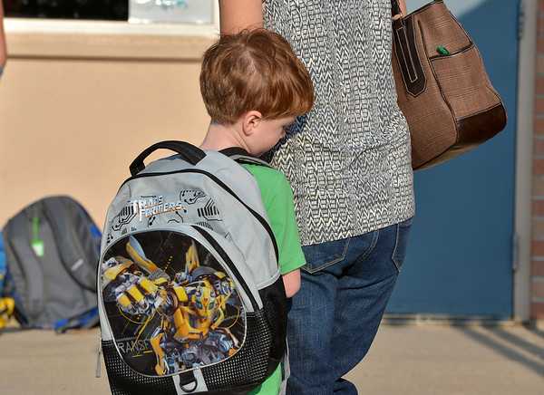 Jamie Grove, 5, stays close to his mother before the start of the first day of kindergarten at Kohl Elementary School on Friday. Curtis' father Philip looks on in the background.<br />  August 17, 2012<br /> staff photo/ David R. Jennings