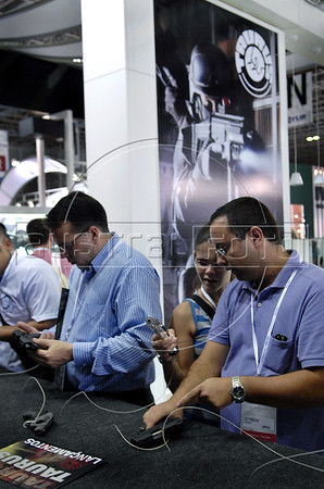 A man looks at a pistol displayed by a brazilian manufacturer at the Latin America Aero and Defence (LAAD) trade show for the defence and security industry in Latin America, Rio de Janeiro, Brazil, April 14, 2011. (Austral Foto/Renzo Gostoli)