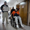 INEWS112-LONG_TERM_CARE.JPG Atlantis Community staffers Larry Williams, center, and Mark Cunningham, right, carry some of Cliff Seigneur's, in wheelchair, belongings out of the North Star Community long-term care facility in west Denver on Nov. 29, 2010. North Star social worker Becky Lane-Ramsey looks on. Seigneur spent six months working with a Denver-area advocacy group, Atlantis Community, to find an accessible apartment and home health care services. (JOE MAHONEY/I-NEWS)