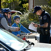 A Louisville police officers gathers information from two cyclists.<br /> Officers search cars and question residents in the Andrew Dr. neighborhood in Superior Sunday afternoon.<br /> The search for missing 10-year-old Jessica Ridgeway of Westminster has shifted to Superior this afternoon after a resident reported the discovery of a backpack with a water bottle that has the girl's name written on it. <br /> Cliff Grassmick  / October 7, 2012