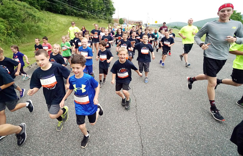 BEN GARVER — THE BERKSHIRE EAGLE<br /> Students from the Lee Elementary School had a police escorted run with the cruisers and officers running with the students from the school through town to the athletic fields where medals are provided by the Lee Police association. For the last three years the Lee Police have hosted a run with the First through Sixth grade at the School called rising runner. The premise is for the students to run laps during their gym class and keep track counting how many miles they do throughout the year. The department works with P.E. teacher Jennifer Carlino as a reward for their hard work the police department would host an escorted run with the cruisers and officers running with the students from the school to the athletic field where medals are provided by the Lee Police association for all that qualified.This year the students ran over a combined 1,000 miles.