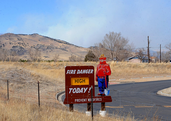 """The Lefthand Canyon Fire burns on the hills in the background of this fire danger sign in north Boulder.<br /> For a videos of the fire, go to  <a href=""""http://www.dailycamera.com"""">http://www.dailycamera.com</a>.<br /> Cliff Grassmick/ March 11, 2011"""