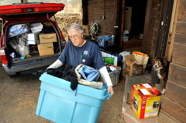 Tom Trask carries his belongings to a truck while evacuating on Friday, March 11, in the Crestview Estates neighborhood area of Boulder. Trask and his wife Veruska lost their home in Summerville during the Fourmile Canyon fire last year.<br /> Jeremy Papasso/ Camera