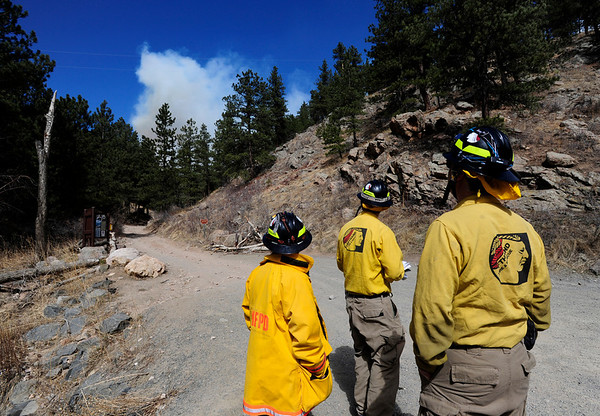 Firefighters from Lefthand Fire Protection District watch the plume of smoke from their initial staging area Friday at Lefthand Canyon Drive and Forest Road 286.<br /> Photo by Marty Caivano/March 11, 2011