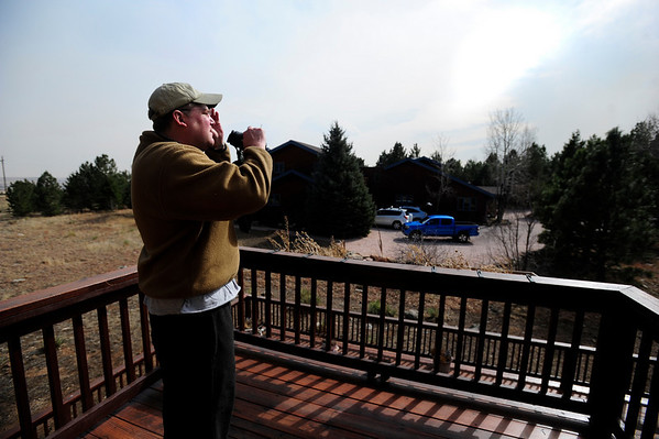 """Glen Gordon watches the Lefthand Canyon Fire from his balcony in the Lake of the Pines neighborhood while collecting his belongings for evacuation on Friday. Gordon says his family has evacuated from their house due to fire """"about half a dozen times"""" in the past ten years. """"The kids kinda like it because the helicopters come to the lake to fill the bucket,"""" Gordon said.<br /> Photo by Marty Caivano/March 11, 2011"""