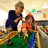 KRISTOPHER RADDER — BRATTLEBORO REFORMER<br /> Linda Whelihan, the education curator at Brattleboro Museum & Arts Center, looks on a creation that Ryder Suponski, 7, brought in during the turn in for the 12th annual Lego Contest & Exhibit at Brattleboro Museum & Arts Center on Tuesday, Nov. 5, 2019. An opening reception and awards ceremony will take place on Thursday, Nov. 7, at 6 p.m.