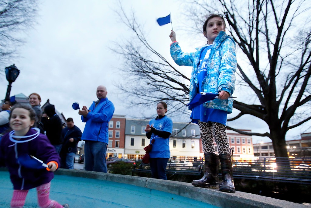 . Olivia Oleskiewicz, 8, stands tall with her blue flag during Hillcrest Educational Centers\' \'Light It Up Blue\' event at Park Square in Pittsfield as part of a global event to raise awareness for Autism. Though the lights at the park never turned on, many gathered to show their support. Friday, April 1, 2016. Stephanie Zollshan � The Berkshire Eagle | photos.berkshireeagle.com