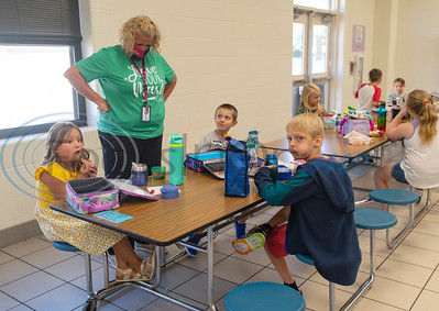 Teacher aide Angela Jett talks with second graders sitting one to two seats apart in the cafeteria during lunch on the first day of school at College Street Elementary School in Lindale on Wednesday, Aug. 19, 2020. The school is following Gov. Abbott's order that children age 10 and under do not have to wear face masks. The school limiting cafeteria use to 50 percent capacity.