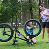 Little Bellas mountain biking mentor, Alison McGee, right, gives Hannah Manzolini, 10, tips on how to check air pressure on tires during the program's pilot week in Pittsfield State Forest.