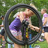 With confidence, Zoey Aubin, 9, prepares to use a hand pump to inflate her mountain bike tires during the Little Bellas mentoring on mountain bikes program.