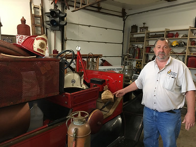 ASHLEY FOX / GAZETTE	 Tom Doyle, a Medina resident, is owner and curator of The Wiz Fire and Historic Medina Museum. Admission to the museum, which Doyle described as his hobby, is free. Here, he is pictured with a 1916 Hallock fire truck.