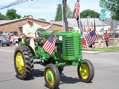 ELIZABETH DOBBINS / GAZETTE Eric Blaich of Liverpool Township drives his tractor during the Memorial Day parade in Valley City. He said both of his grandfathers were veterans: John Marx, who served in the military police, and Russell Blaich, who served in the army.
