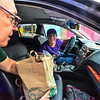 KRISTOPHER RADDER — BRATTLEBORO REFORMER<br /> Diana Bander smiles while donating a bag of food that Gregory Kanetis, from H&R Block, collects during the 10th annual Load the Latchis event on Thursday, Aug. 22, 2019.