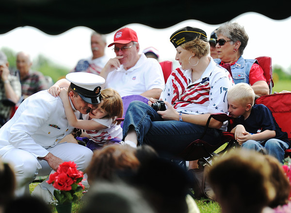 Globe/T. Rob Brown<br /> Ret. U.S. Navy Senior Chief Mark Buresh (left) of Carthage gets a hug from his 6-year-old daughter Elizabeth just before speaking during Memorial Day services, Monday, May 27, 2013, at Park Cemetery in Carthage. To the right are Buresh's wife, Lori, and 5-year-old son William.