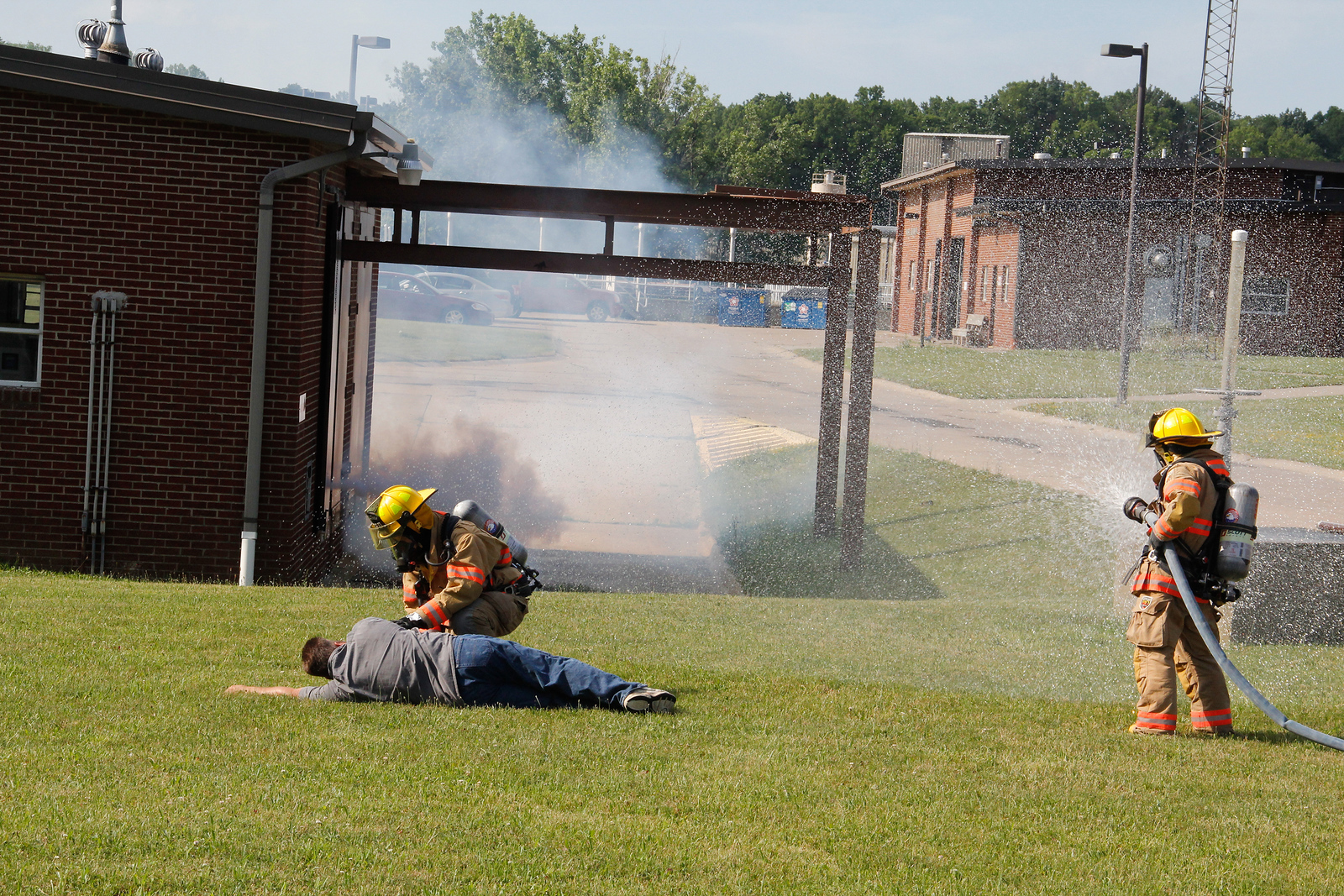 ALEC SMITH / GAZETTE Valley City Fire Department officials in Liverpool Township work Saturday on a simulated exercise involving a mock disaster. The event in which workers demonstrated skills in the event of a chlorine release, took place at the Liverpool Waste Water Treatment Plant, 89 Columbia Road. Here is Rob Baldauf from Lodi on the left acting as a victim, being checked by Ian Martin, of Brunswick, from the Valley City Fire Department. Holding the hose at right is Darby Sandor of the Valley City Fire Department .