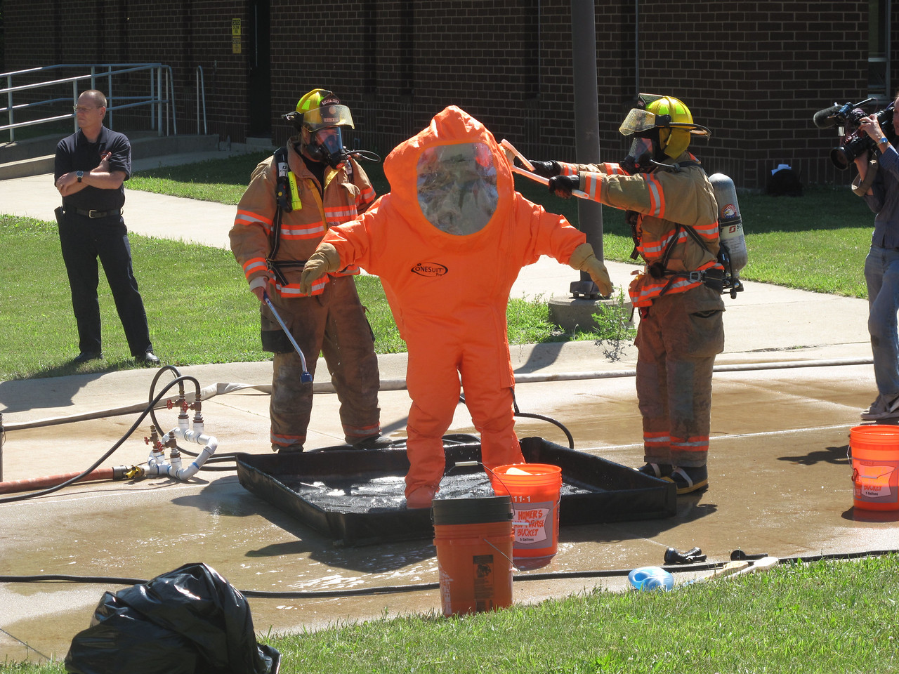 BOB FINNAN / GAZETTE A hazardous materials worker is scrubbed and hosed down after coming from the mock chlorine spill at the Liverpool Waste Water Treatment Plant Saturday during the mass casualty incident.