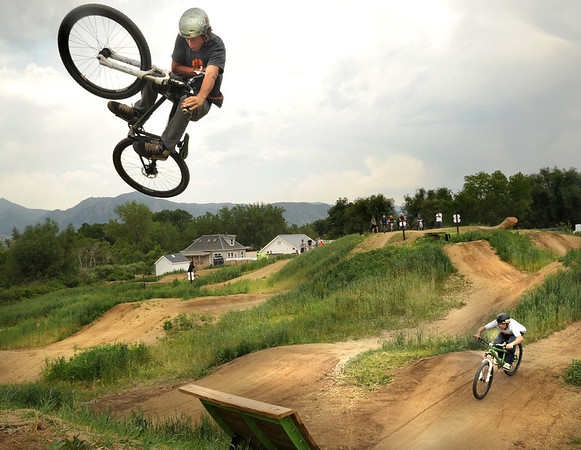 "Jacob Hyde, of Santa Cruz, C.A., left, goes big over a ramp while being followed by a friend on Saturday, June 11, at the new Valmont Bike Park in Boulder. Hyde works for Alpine Bike Parks and helped build the Valmont Bike Park. For more photos and a video of the bike park's opening day go to  <a href=""http://www.dailycamera.com"">http://www.dailycamera.com</a><br /> Jeremy Papasso/ Camera"