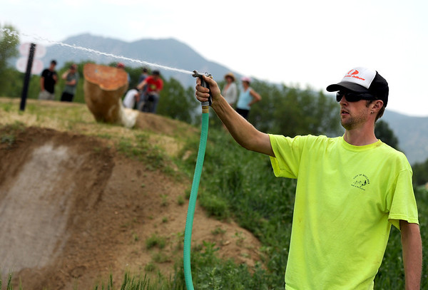 "Maintenance crew worker Tarka Wilcox sprays down the trails to help with the dust on Saturday, June 11, at the new Valmont Bike Park in Boulder. For more photos and a video of the bike park's opening day go to  <a href=""http://www.dailycamera.com"">http://www.dailycamera.com</a><br /> Jeremy Papasso/ Camera"