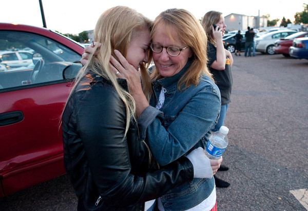 Emma Goos, 19, hugs her mother, Judy Goos, outside Gateway High School where witnesses were brought for questioning Friday, July 20, 2012, in Aurora, Colo. Emma was in the third row of the theater of the new Batman movie when the shooter entered. She helped apply pressure to a man's head who was injured. (AP Photo/Barry Gutierrez)