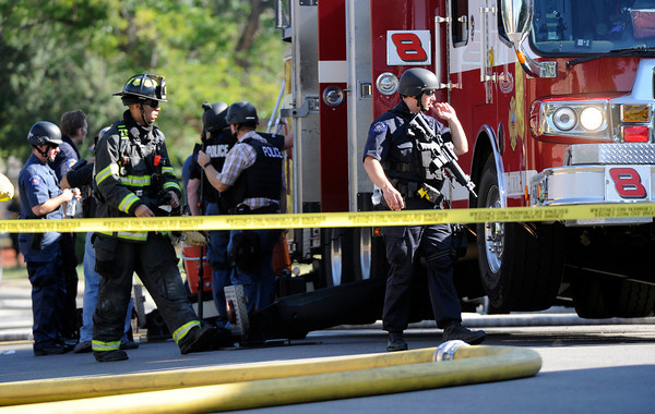 Law enforcement officials gather behind a fire truck as they search the home where the suspect in a shooting at a movie theatre lived in Aurora, Colo., Friday, July 20, 2012.  A gunman wearing a gas mask set off an unknown gas and fired into the crowded movie theater killing 12 people and injuring at least 50 others, authorities said.  (AP Photo/The Denver Post,  Cyrus McCrimmon) TV, INTERNET AND MAGAZINES CALL FOR RATES AND TERMS