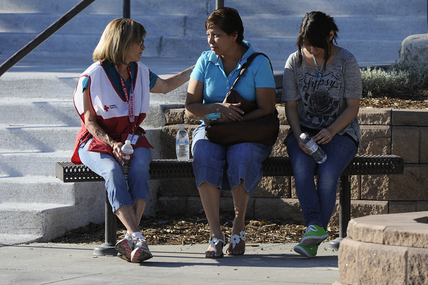 Betha Larios and her daughter, Fatima, 14, talk with a Red Cross volunteer at Gateway High School in Aurora, Colo, where witnesses we being interviewed by authorities Friday July 20, 2012.  A gunman wearing a gas mask set off an unknown gas and fired into the crowded movie theater killing 12 people and injuring at least 50 others, authorities said. (AP Photo/The Denver Post, Craig F. Walker) TV, INTERNET AND MAGAZINES CALL FOR RATES AND TERMS