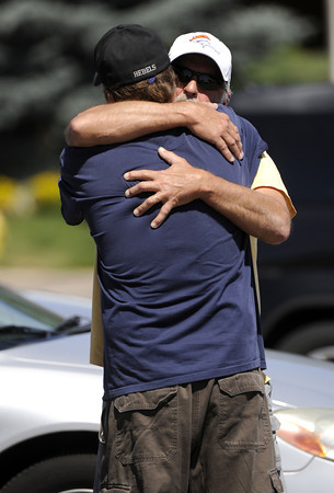 Two men hug outside Gateway High School in Aurora, Colo., where witnesses are being interviewed by authorities Friday, July 20, 2012. A  gunman wearing a gas mask set off an unknown gas and fired into the crowded movie theater killing 12 people and injuring dozens, authorities said.  The suspect is identified as 24-year-old James Holmes.(AP Photo/The Denver Post, Craig F. Walker) TV, INTERNET AND MAGAZINES CALL FOR RATES AND TERMS