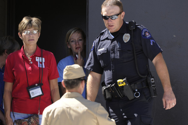A young woman peers from the entrance at Gateway High School in Aurora, Colo., where witnesses we being interviewed by authorities Friday, July 20, 2012.  A gunman wearing a gas mask set off an unknown gas and fired into the crowded movie theater killing 12 people and injuring at least 50 others, authorities said.  The suspect is identified as 24-year-old James Holmes. (AP Photo/The Denver Post, Craig F. Walker) TV, INTERNET AND MAGAZINES CALL FOR RATES AND TERMS