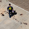 An ATF agent walks around blood stains on the sidewalk at the back of a movie theater after a shooting Friday, July 20, 2012 in Aurora, Colo.  A gunman wearing a gas mask set off an unknown gas and fired into the crowded movie theater killing 12 people and injuring at least 50 others, authorities said. (AP Photo/The Denver Post, Helen H. Richardson) TV, INTERNET AND MAGAZINES CALL FOR RATES AND TERMS