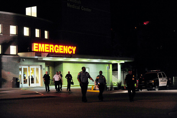 Denver Police Officers and others walk outside of the Swedish Medical Center just hours after a shooting at an Aurora movie theatre Wednesday, July, 19, 2012 during a perimeter showing of the new Batman movie. Twelve people were fatally shot and about 50 people other people were shot and wounded and taken to hospitals around the Denver area. Swedish Medical Center brought in three victims.<br /> Heather Rousseau, The Denver Post