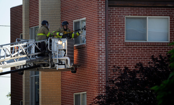 Police break out a window of an apartment  where the suspect in a shooting at a movie theatre lived in Aurora, Colo., Friday, July 20, 2012. As many as 12 people were killed and 50 injured at a shooting at the Century 16 movie theatre early Friday during the showing of the latest Batman movie. (AP Photo/The Denver Post, Cyrus McCrimmon) TV, INTERNET AND MAGAZINES CALL FOR RATES AND TERMS