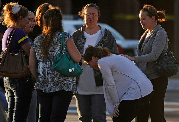 A group of friends are overcome with emotion as they gather outside Gateway High School, Friday July 20, 2012, in Aurora. They got news that their friend was killed during a shooting, where about 50 people were shot 12 fatally early Friday inside an Aurora movie theater during a premiere showing of the new Batman movie, were taken to the high school by bus to be questioned by police. RJ Sangosti, The Denver Post