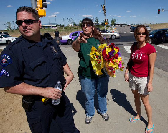 Tonya Goodman, center, and her friend Terry Morales, right, talk with Aurora Police Det. Mike Gerbino, left, about where they can leave flowers, Friday, July 20, 2012, near the movie theater in Aurora, Colo., where a gunman killed at least 12 people and wounded dozens of others in one of the deadliest mass shootings in recent U.S. history. (AP Photo/Ted S. Warren)