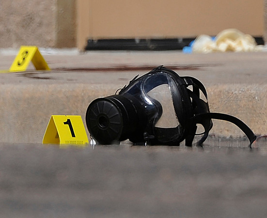 A gas mask was marked as the first piece of evidence in a criminal investigation outside the parking lot behind the Century 16 movie after a shooting at the theatre Friday, July 20,2012. A gunman wearing a gas mask set off an unknown gas and fired into the crowded movie theater killing 12 people and injuring at least 50 others, authorities said.  The suspect is identified as 24-year-old James Holmes. (AP Photo/The Denver Post, Karl Gehring) TV, INTERNET AND MAGAZINES CALL FOR RATES AND TERMS