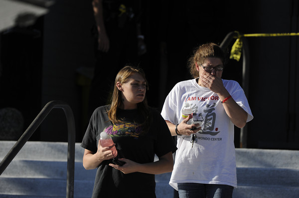 Kimberly Sinkiewicz, left, and Rachel Frangis leave Gateway High School in Aurora, Colo., where witnesses we being interviewed by authorities Friday July 20, 2012.  A gunman wearing a gas mask set off an unknown gas and fired into the crowded movie theater killing 12 people and injuring at least 50 others, authorities said. (AP Photo/The Denver Post, Craig F. Walker) TV, INTERNET AND MAGAZINES CALL FOR RATES AND TERMS