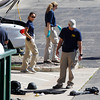 Investigators look over evidence on ground outside the back door of the Century 16 movie theater east of the Aurora Mall in Aurora, Colo. on Friday, July 20, 2012. A gunman in a gas mask barged into a crowded Denver-area theater during a midnight showing of the Batman movie on Friday, hurled a gas canister and then opened fire in one of the deadliest mass shootings in recent U.S. history. (AP Photo/David Zalubowski)