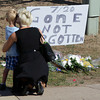 "A woman and a child stand near a sign that reads ""7/20 Gone Not Forgotten,"" near the movie theater where a gunman killed at least 12 people and wounded dozens of others in one of the deadliest mass shootings in recent U.S. history, Friday, July 20, 2012 in Aurora, Colo. The pair left their flowers next to the sign. (AP Photo/Ted S. Warren)"