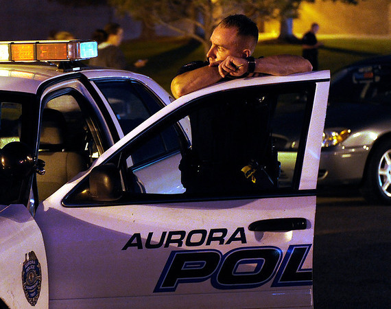 An Aurora Police officer waited outside Gateway High School where witnesses continued to be questioned Friday morning. Aurora Police responded to the Century 16 movie theatre early Friday morning, July 20, 2012. Twelve persons were killed when a lone shooter opened fire inside the theatre during a midnight screening of The Dark Knight Rises. Karl Gehring/The Denver Post