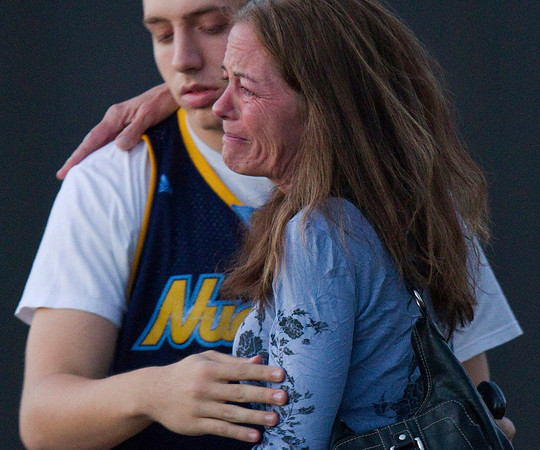 "Jacob Stevens, 18, hugs his mother Tammi Stevens after being interview by police outside Gateway High School where witness were brought for questioning after a shooting at a movie theater, Friday, July 20, 2012 in Denver. A gunman wearing a gas mask set off an unknown gas and fired into a crowded movie theater at a midnight opening of the Batman movie ""The Dark Knight Rises,"" killing at least 12 people and injuring at least 50 others, authorities said. (AP Photo/Barry Gutierrez)"