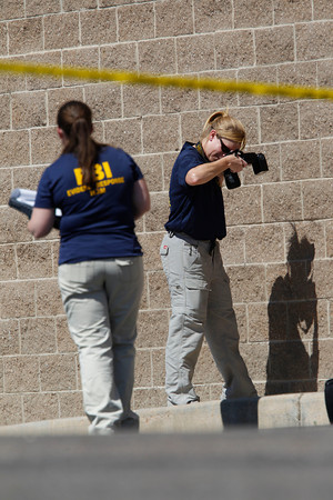 Investigators take photographs of evidence outside the Century 16 movie theater east of the Aurora Mall in Aurora, Colo. on Friday, July 20, 2012. A gunman in a gas mask barged into the crowded Denver-area theater during a midnight showing of the Batman movie on Friday, hurled a gas canister and then opened fire in one of the deadliest mass shootings in recent U.S. history. (AP Photo/David Zalubowski)