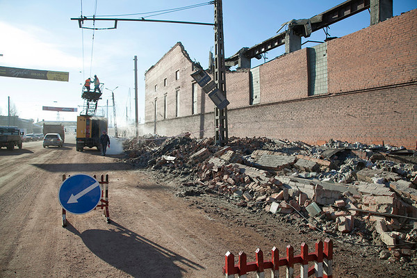 In this photo provided by Chelyabinsk.ru municipal workers repair damaged electric power circuit outside a zinc factory building with about 600 square meters (6000 square feet) of a roof collapsed  after a meteorite exploded over in Chelyabinsk region on Friday, Feb. 15, 2013 A meteor streaked across the sky of Russia's Ural Mountains on Friday morning, causing sharp explosions and reportedly injuring around 100 people, including many hurt by broken glass. (AP Photo/ Oleg Kargapolov, Chelyabinsk.ru)