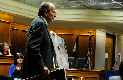 MIDYETTE Thomas Carberry, an attorney for Molly Midyette, shows photographs of Midyette with her baby to the prosecution before submitting them into evidence during Midyette's hearing on Monday.  PHOTO BY MARTY CAIVANO OCT.24, 2011