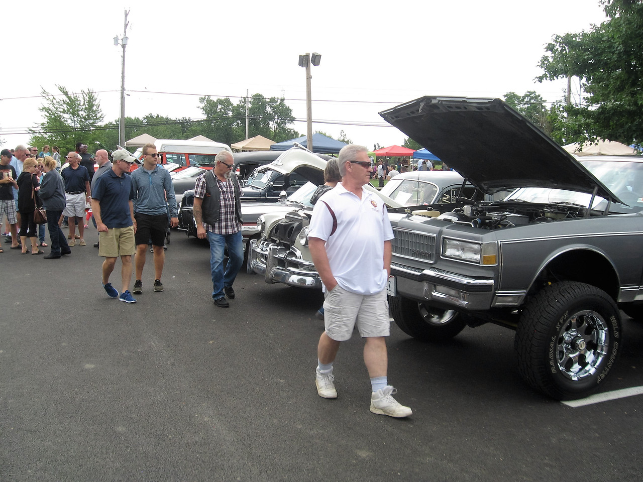 BOB SANDRICK / GAZETTE Hundreds of visitors to Mapleside Farms check out more than 60 classic and antique cars on Sunday during a peach festival event.