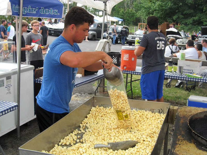 BOB SANDRICK / GAZETTE Manny Clement, a worker at Mapleside Farms, serves up kettle corn Sunday at the Mapleside Farm Peach Fest & Car Show in Brunswick.