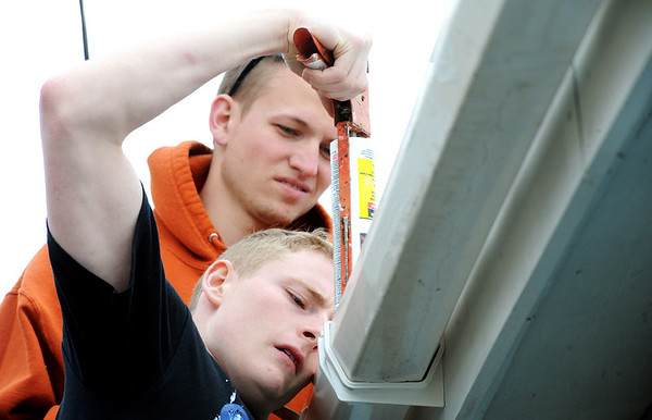 Globe/T. Rob Brown<br /> Johnnie Day, of Mosheim, Tenn., uses a caulking gun as Andrew Julian looks on, while they repair rooftop guttering at a Joplin home in the 2300 block of South Ozark Wednesday afternoon, March 7, 2012. The Baptist Collegiate Ministry students from Walters State Community College in Morristown are utilizing their spring break to visit Joplin to help those affected by the May 22, 2011, tornado.