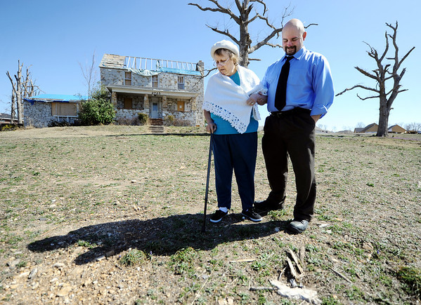 "Globe/T. Rob Brown<br /> Ray Goodman, of Columbia, and his mother, Yvonne Goodman, look down in memory at what's left of a rock base where Ray Goodman's father, Jess ""J.T."" Goodman, had anchored a U.S. flag in front of their Joplin home Friday afternoon, March 9, 2012, near Schifferdecker Avenue and 32nd Street. Jess ""J.T."" Goodman died following the May 22, 2011, tornado."