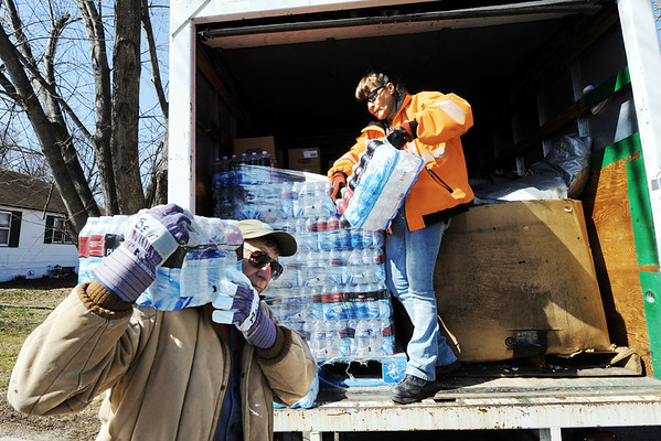 Globe/T. Rob Brown<br /> Bently Adams, left, of Georgetown, Ind., carries a case of water as Kiki Sagot of Saginaw, both volunteers with Home Missions in Joplin, move water from the back of a truck to anyone needing it in the 400 block of Fieldcrest Wednesday morning, Feb. 29, 2012, in Pittsburg, Kan.