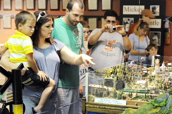 "Globe/T. Rob Brown<br /> Susan Chambers, left, holds four-year-old Trevis Moore, as they look at a model train layout with Moore's father, Jeremy Moore, during a model train show at the Joplin Museum Complex at Schifferdecker Park. ""He loves trains,"" Jeremy Moore said. ""One time, he asked us to chase a real train down several times so he could watch it go by."" In the background, fellow show visitors Nick Ybarra of Joplin takes a photo of the train diorama as friend Kyle Feagins, 11, of Fort Scott, Kan., looks on."