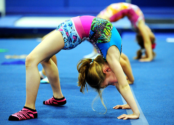 Globe/T. Rob Brown<br /> Seven-year-old Vivian Farber stretches during class Tuesday evening, March 13, 2012, at the new Amplify Gymnastics & Cheer facility in the Joplin Industrial Park.